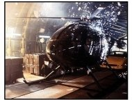 Die Another Day movie still: Sparks rain down on a helicopter while the cargo plane carrying it disintegrates in Die Another Day